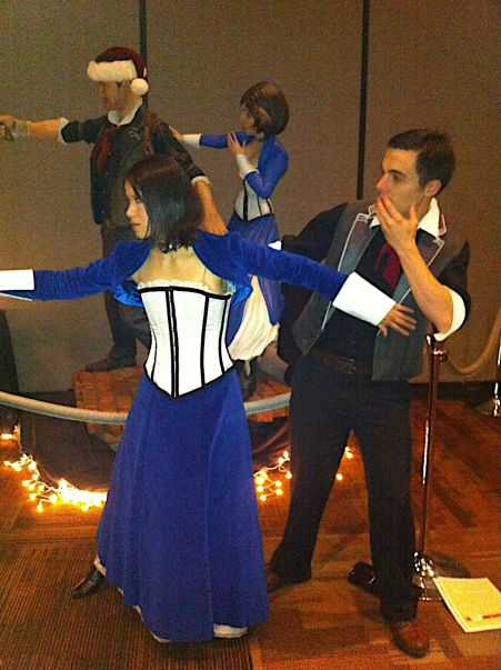 Elizabeth and Booker cosplayers posing with Bioshock Infinite statue at Child's Play 2013